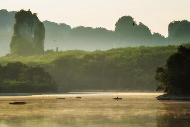 Pescador de silhueta no lago enevoado