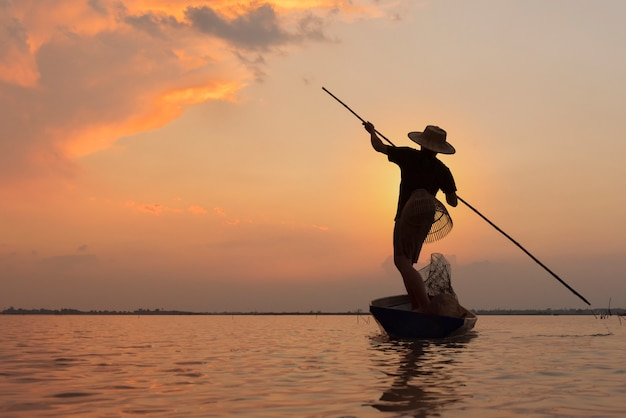 Pescador de silhueta remar em água doce no pôr do sol