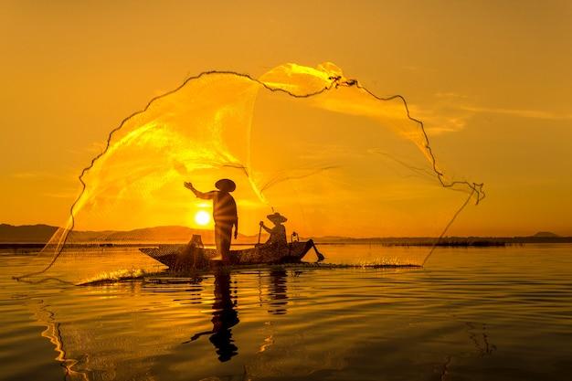Pescador do lago bangpra na ação ao pescar tailândia.
