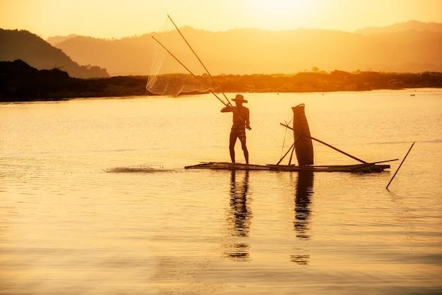 Pescador do rio mekong em ação ao pescar, tailândia