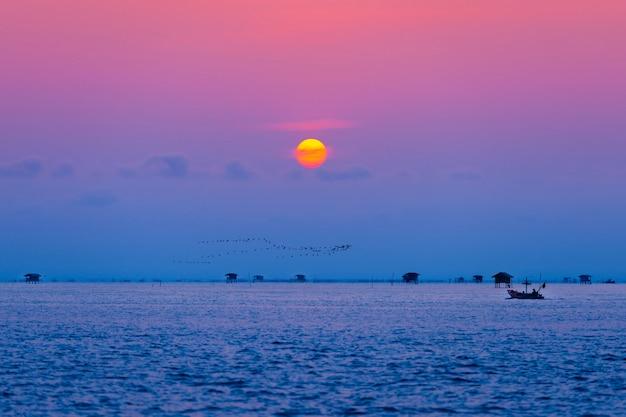 Pescador e vila flutuante no oceano ao amanhecer