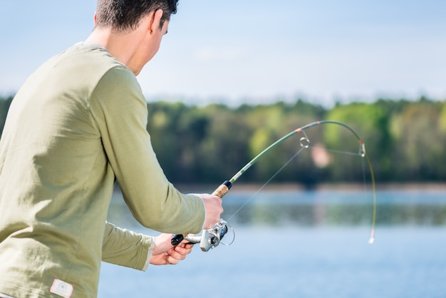Pescador em lago pescando por esporte tentando puxar um peixe para dentro