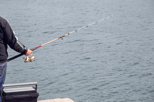 Pescador em pé na beira da doca com vara de pescar perto do mar em dia ensolarado.