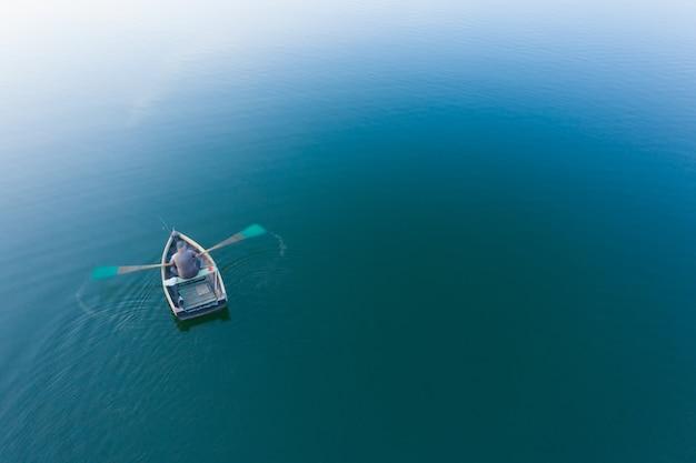 Pescador em um barco de madeira rema, vista superior. foco suave.
