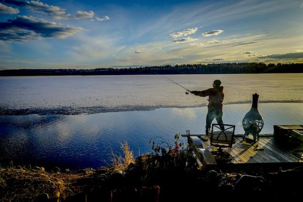 Pescador em um cais, captura de peixes durante um dia ensolarado e bonito