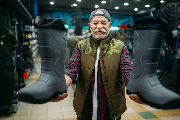 Pescador escolhendo botas de borracha em loja de pesca