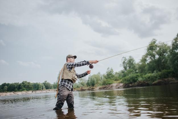 Pescador está parado em águas rasas e pesca. ele está jogando a colher para a frente. cara tem haste de mosca nas mãos. ele está usando isso. homem usa limícolas, colete e boné para proteger o corpo.