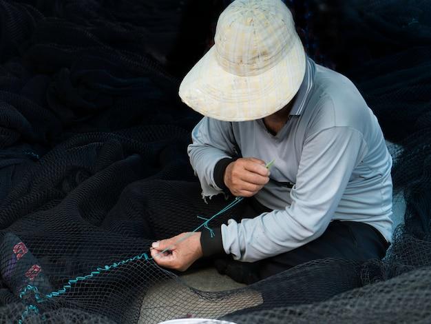 Pescador está reparando redes de pesca.