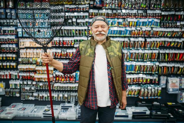 Pescador feliz segura a rede em uma loja de pesca, ganchos e bugigangas