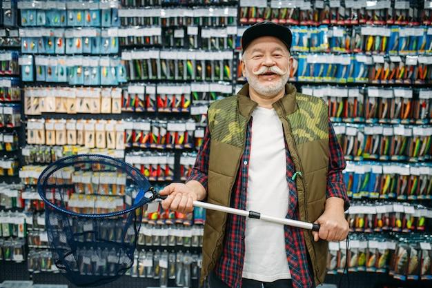 Pescador feliz segurando rede em loja de pesca