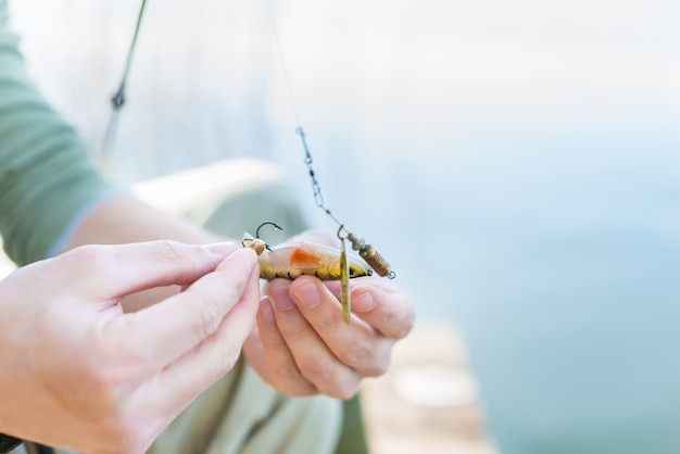 Pescador fixando isca no casco da vara de pescar