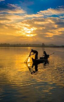 Pescador jogando rede no início da manhã perto da ponte u bein, nascer do sol, lago taungthaman perto de amarapura, mianmar.