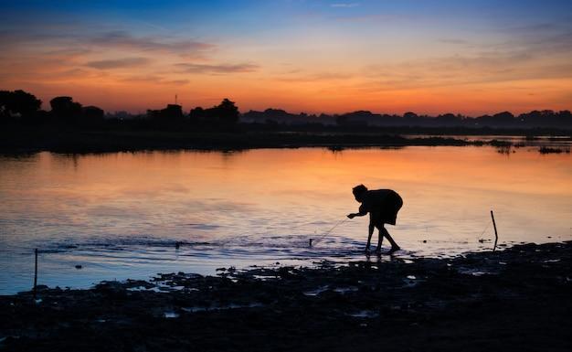 Pescador jogando rede no lago taungthaman no início da manhã