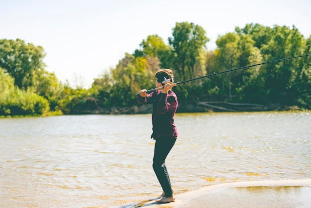 Pescador jovem adolescente em casual captura de peixes na margem do rio com vara num dia de verão
