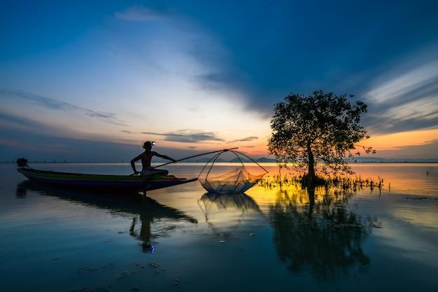 Pescador, ligado, barco, pegando peixe, com, amanhecer