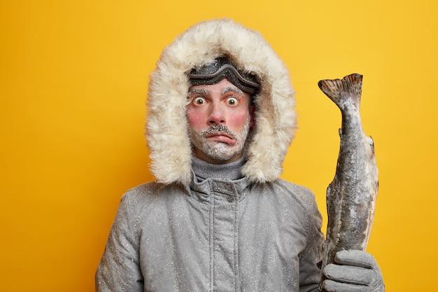 Pescador masculino congelado e perplexo faz expedição de inverno no norte.