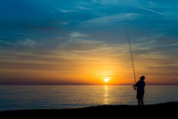 Pescador na praia ao pôr do sol