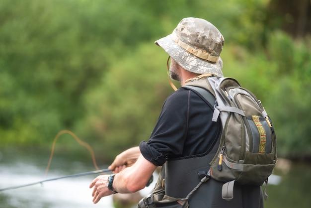 Pescador pesca no rio, segurando a vara de pesca.