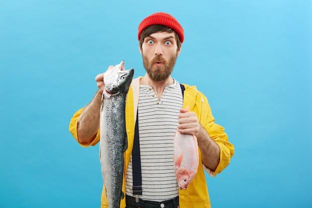 Pescador profissional segurando dois peixes nas mãos e regozijando-se com o sucesso