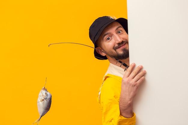 Pescador, segurando a vara de pescar e posando enquanto sorrindo