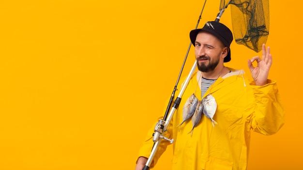Pescador segurando a vara de pescar e rede com espaço de cópia