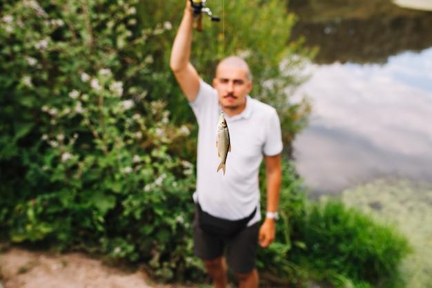 Pescador, segurando, fresco, pegado, peixe, em, ao ar livre