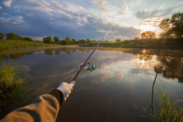 Pescador segurando sua vara de pescar no início da manhã