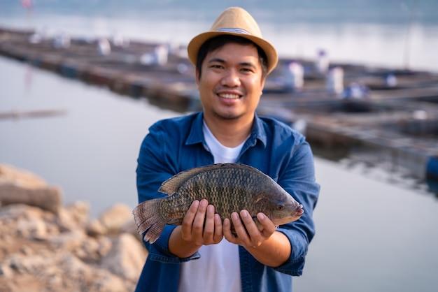 Pescador segurando um grande peixe tilápia à beira-mar