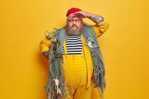 Pescador sério barbudo mantém a mão na testa e olha para longe, posa com rede de pesca nos ombros, pega criaturas marinhas, tem barriga grande, braços tatuados