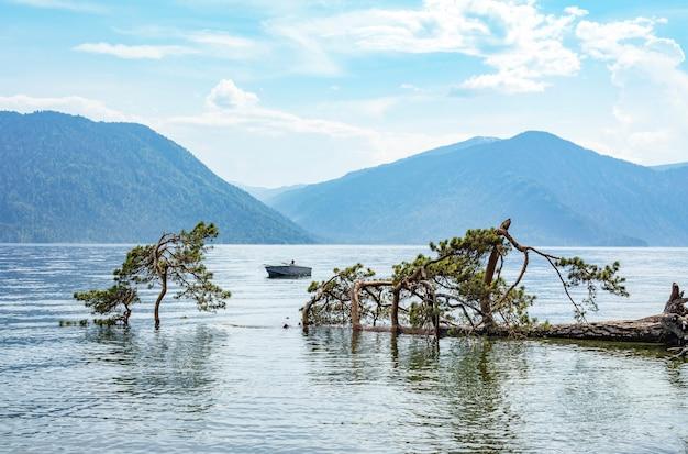 Pescador solitário em um velho barco no lago teletskoye. montanhas de altai em um dia nublado