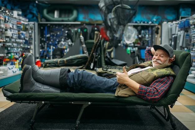 Pescador sorridente deitado em uma espreguiçadeira em uma loja de pesca com ganchos e bugigangas