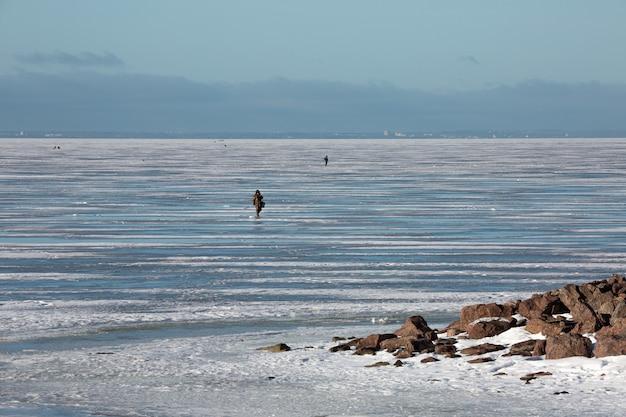 Pescadores caminhando na costa gelada do golfo da finlândia.