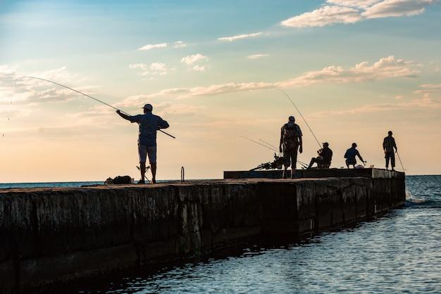 Pescadores com varas de pesca jogam isca na água no cais do mar