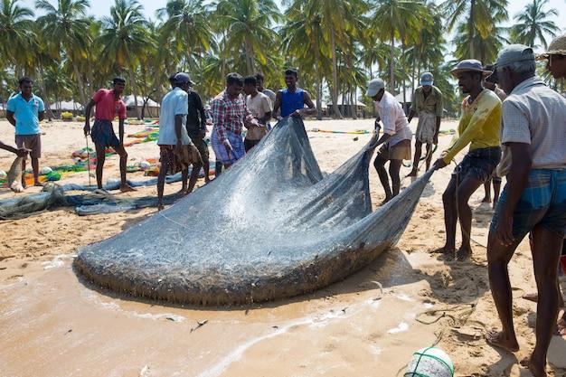 Pescadores locais puxam uma rede de pesca do oceano índico em mach