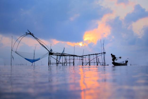 Pescadores na pesca de barco com uma rede de pesca, o equipamento tradicional velho da pesca tailandesa. cena da silhueta na vila de pak pra, província de pattalung, tailândia.