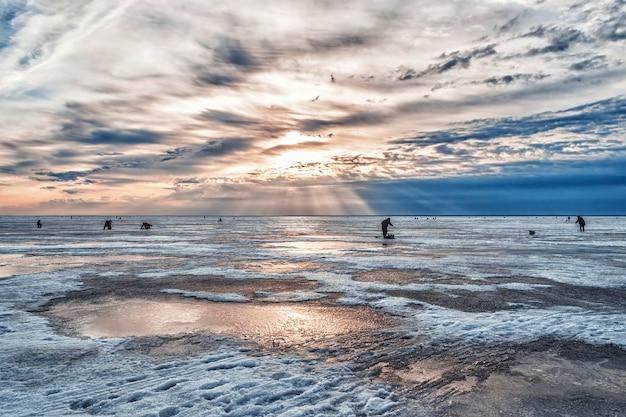 Pescadores pescando ao amanhecer em uma manhã gelada de inverno