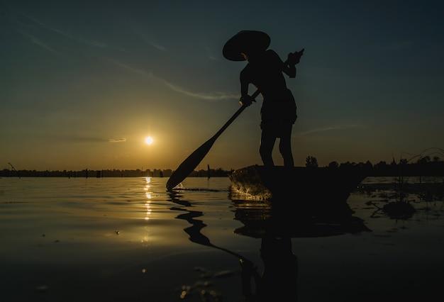 Pescadores que usam redes de pesca, pescadores que pescam na luz dourada do amanhecer.