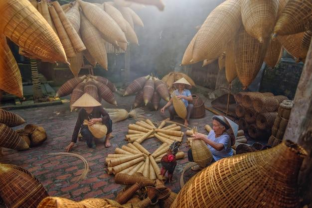 Pescadores vietnamitas estão fazendo cestaria para equipamentos de pesca de manhã em thu sy village, vietnã