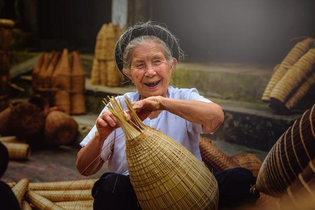 Pescadores vietnamitas estão fazendo cestaria para equipamentos de pesca de manhã em thu sy village