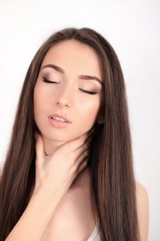 Pescoço cansado mulher nova bonita que sofre da dor de garganta. sentimento feminino atraente cansado, esgotado, estressado. menina, massageando o pescoço doloroso com a mão. corpo e conceito de cuidados de saúde.