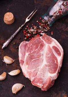Pescoço de bife de carne de porco crua em um fundo escuro