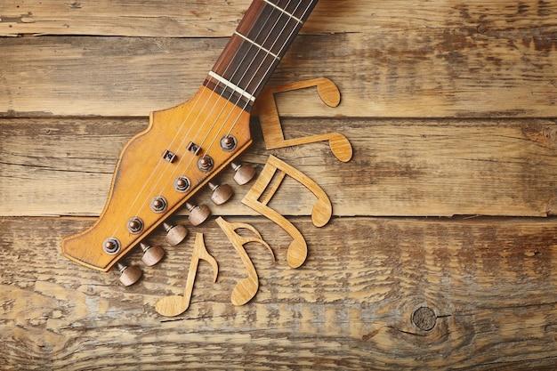 Pescoço de guitarra e notas musicais em superfície de madeira