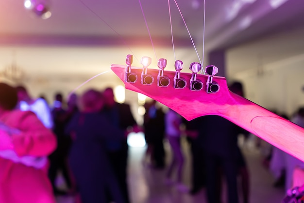 Pescoço de guitarra no fundo de pessoas dançando.