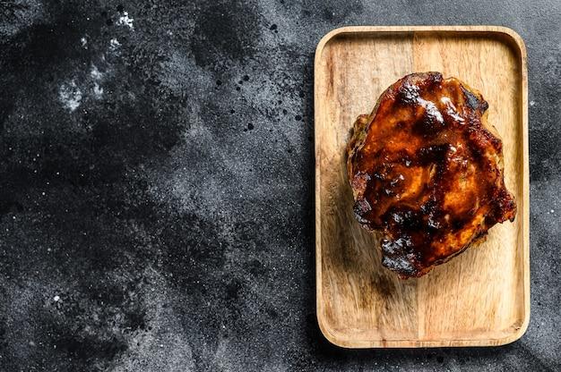 Pescoço de porco assado com especiarias na tábua. fundo preto. vista do topo. copie o espaço.