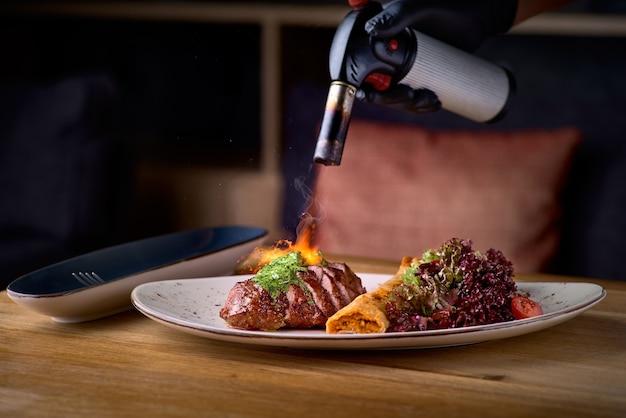 Pescoço de porco com rolo de grão de bico e salada. prato principal do restaurante com carne bem passada, vitela ou bife de vaca
