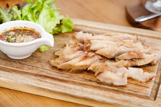 Pescoço de porco cozido no carvão com o molho tem sabor azedo picante é um aperitivo popular na tailândia.