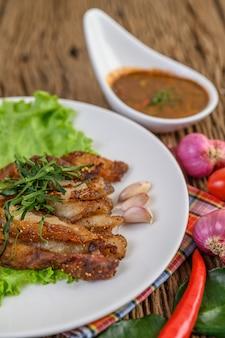Pescoço de porco grelhado em um prato branco com cebola roxa, tomate e pimentão em cima da mesa de madeira.