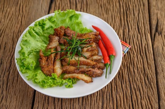 Pescoço de porco grelhado em um prato branco sobre uma mesa de madeira.