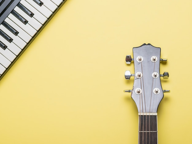 Pescoço de violão acústico e teclas de piano em uma superfície amarela