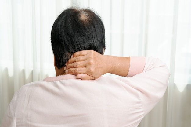 Pescoço e dor no ombro, velha mulher que sofre de lesão no pescoço e no ombro, conceito de problema de saúde